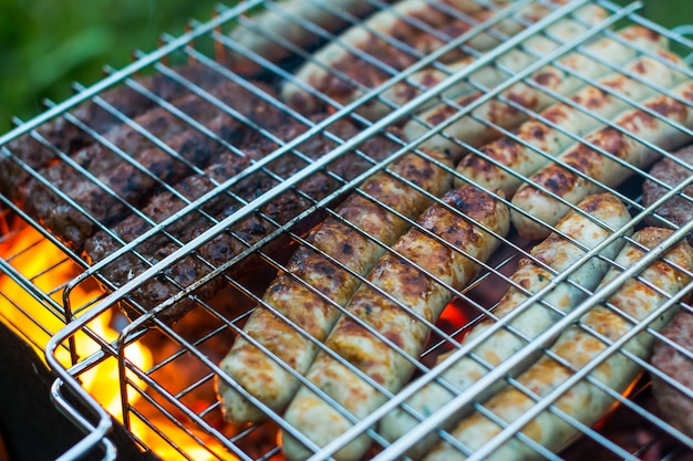 Raw pork sausages roasted on the grill, barbecue season outdoors. meat roasting at barbecue.