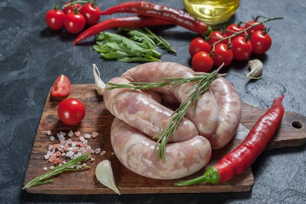 Сырые свиные колбаски с чили и помидорами на разделочной доске