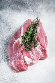 Сырое мясо лопатки свинины на столе мясника. белый стол. вид сверху.