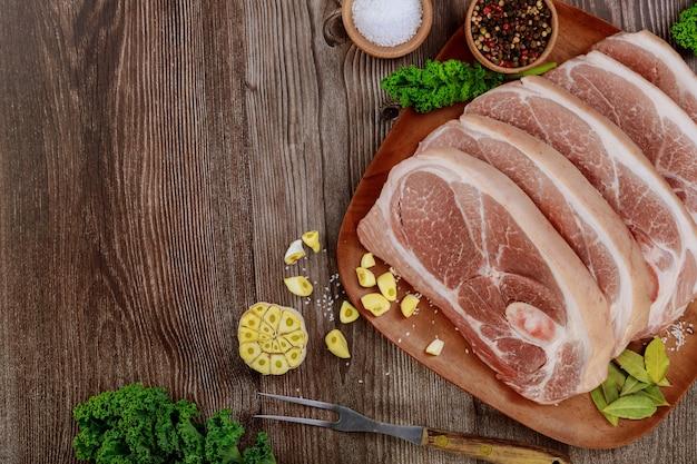 Сырая свиная лопатка, нарезанная кожей и костью на деревянном столе