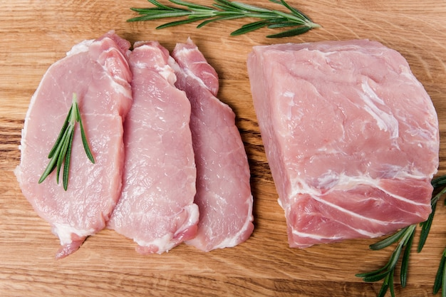 Raw pork sliced meat with rosemary on the wooden board. flat lay on the wooden table