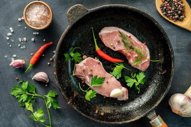 부엌에서 뜨거운 프라이팬에 원시 돼지 고기 슬라이스 또는 스테이크, 소박한 사진 스타일 witj 성분