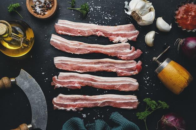 Кусочки сырой свинины со специями на темноте. готов к приготовлению