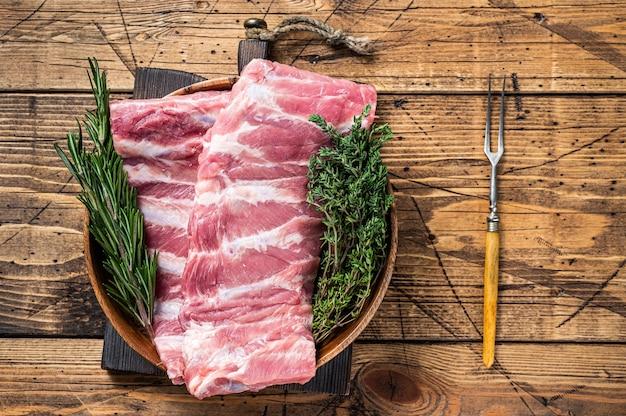 나무 접시 witn 고기 포크에 원시 돼지 갈비