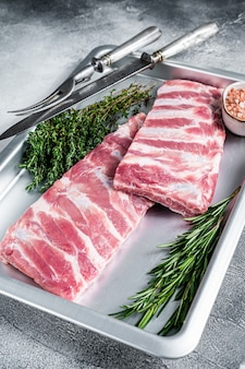 Raw pork spare ribs in kitchen tray with herbs