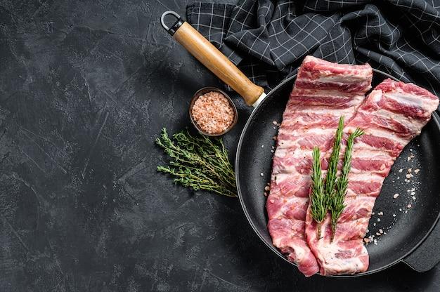 Сырые свиные ребрышки со специями и зеленью на сковороде