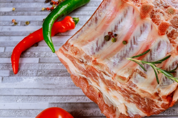 Raw pork steak ready for cooking with herbs. gray cutting boards.