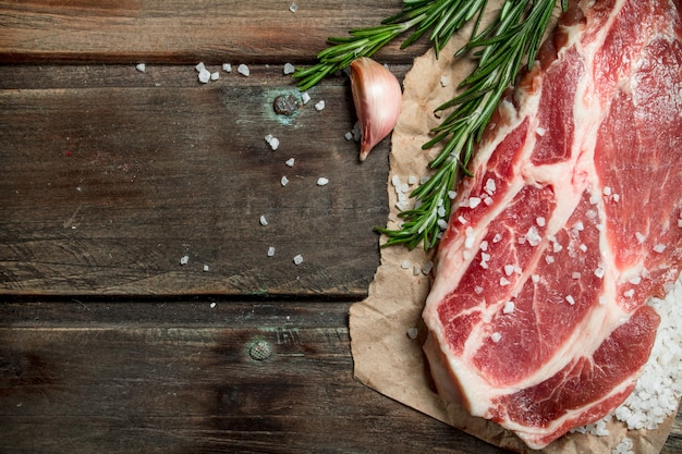 Raw pork steak with fragrant rosemary. on a wooden background.