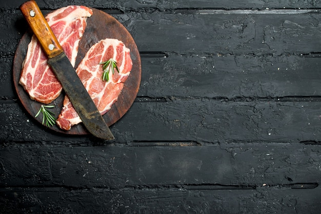 Raw pork steak with an old knife on cutting board on black rustic table.