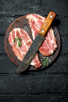 Raw pork steak with an old knife on cutting board on rustic table.