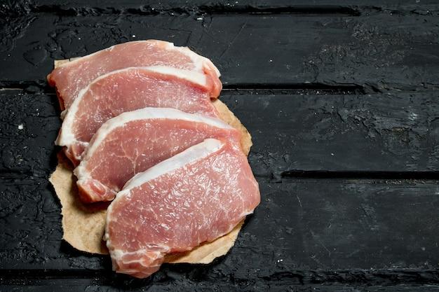 Сырые стейки из свинины на старой бумаге. на черном деревенском фоне.