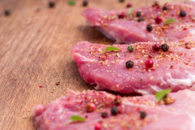 Raw pork steaks sprinkled with spices and herbs