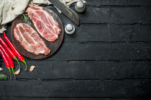 Raw pork steaks with aromatic and herbs and spices. on a black rustic table.