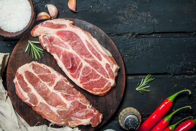 Raw pork steaks with aromatic and herbs and spices on dark rustic table.