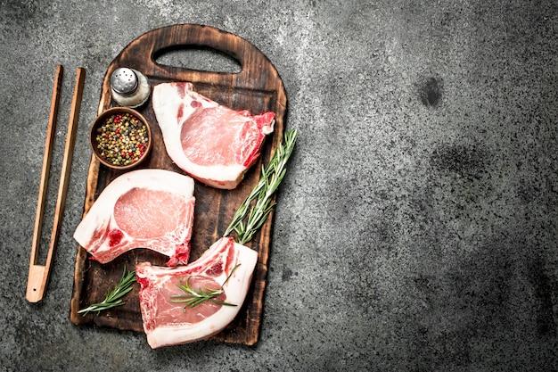 허브와 향신료와 함께 원시 돼지 고기 스테이크. 소박한 배경.