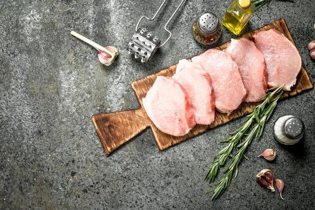 Сырые стейки из свинины с травами и специями. на деревенском фоне.