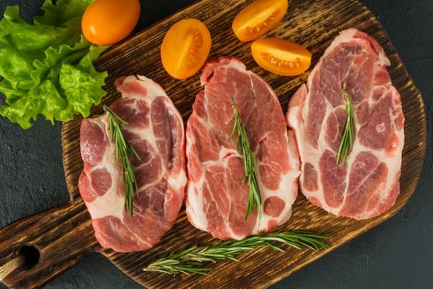 Сырые стейки из свинины с розмарином и помидорами. свинина свежая. шейный стейк. органическое мясо кето и палеодиета.