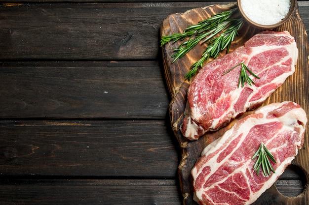 나무 테이블에 로즈마리와 원시 돼지 고기 스테이크입니다.