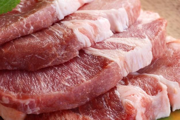 Сырые свиные стейки с солью и перцем