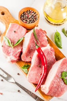 Raw pork steaks with spices, herbs and olive oil