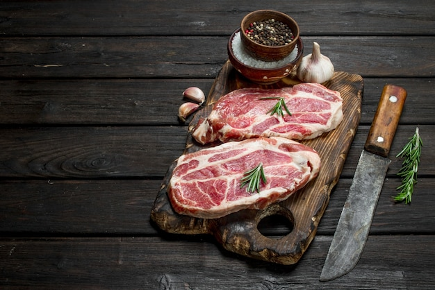 Raw pork steaks with spices on wooden table.