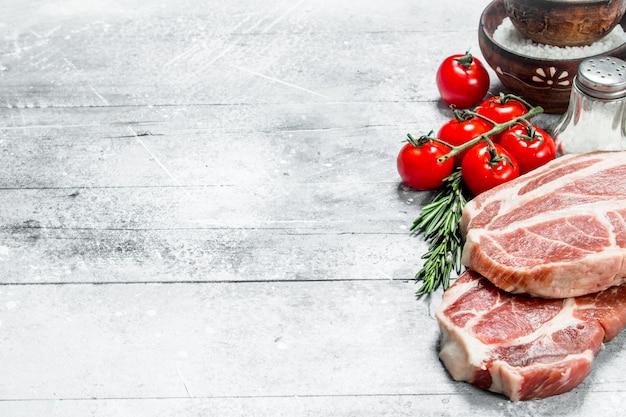 生のポークステーキとトマトと唐辛子。素朴な背景に。