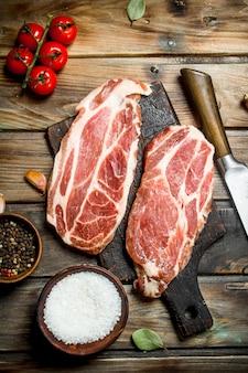 토마토와 나무 테이블에 향신료와 원시 돼지 고기 스테이크.