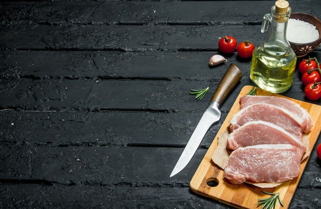Raw pork steaks with tomatoes and spices. on a black rustic background.