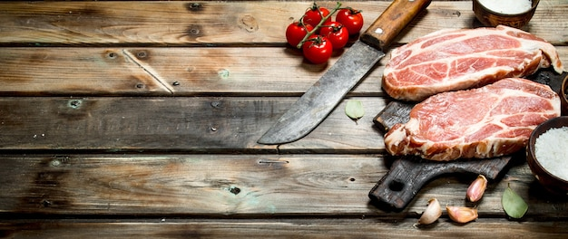 Raw pork steaks with tomatoes and spices. on a wooden background.