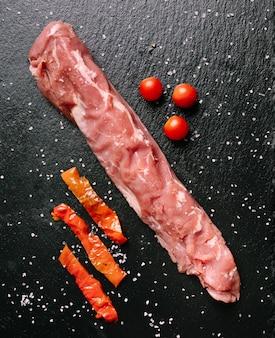 Сырая свиная вырезка на грифельной тарелке с перцем и помидорами