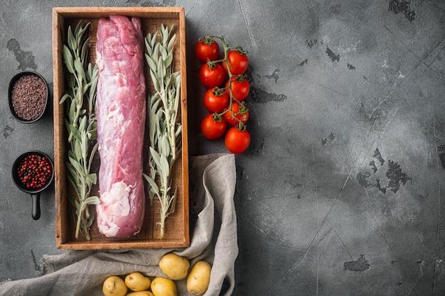 Сырая свиная вырезка с ингредиентами и набором зелени, в деревянной коробке, на сером камне