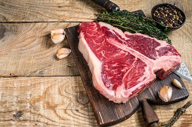 나무 커팅 보드에 허브와 함께 원시 porterhouse 또는 t-bone 쇠고기 고기 스테이크. 나무 배경입니다. 평면도. 공간을 복사하십시오.