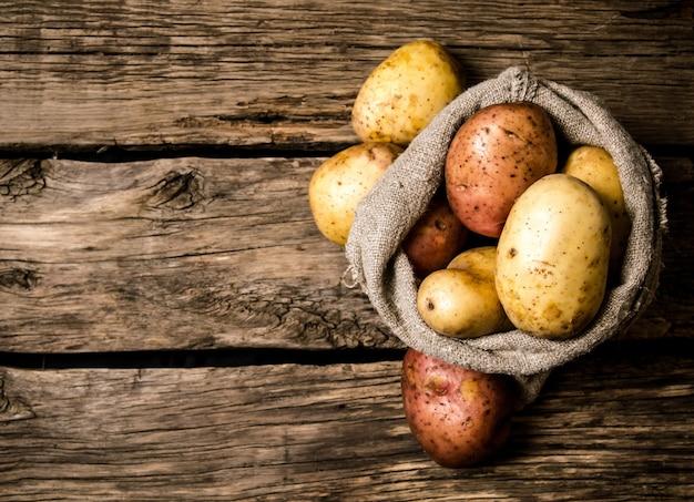 생 감자 식품. 나무 배경에 오래 된 자루에 신선한 감자. 텍스트 무료 장소. 평면도