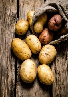 생 감자 식품. 나무 테이블에 오래 된 자루에 신선한 감자.