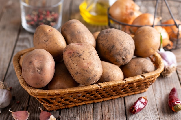 生のジャガイモ食品。木製の背景に新鮮なジャガイモ