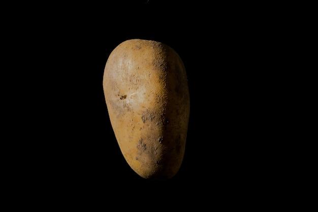 Сырой картофель на черном фоне