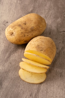 Raw potato and sliced potato over wood background