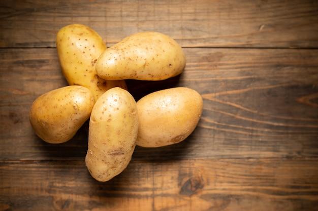 Raw potato on wooden background.
