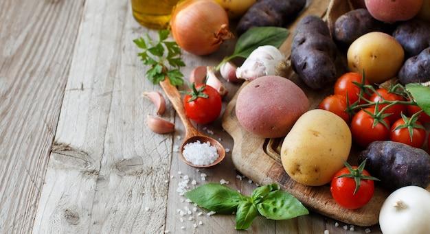 木の板に生のジャガイモと野菜