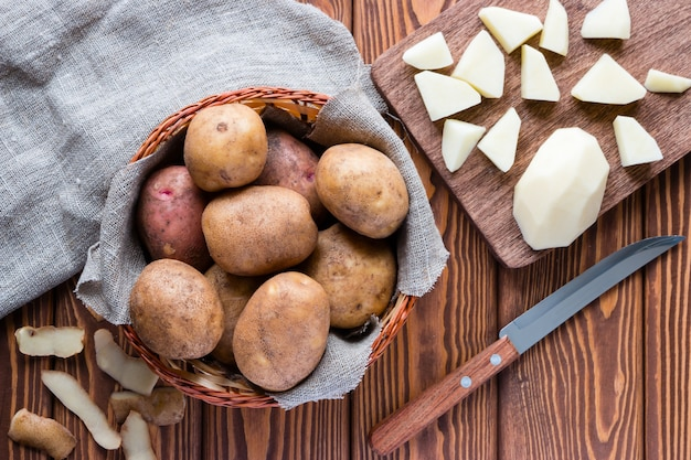 Raw potatoes in the basket, and peeled potatoes on a cutting board