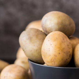 Raw potatoes in bowl close-up