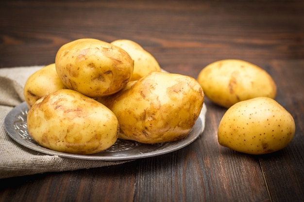 Raw potatoes on a brown wooden background