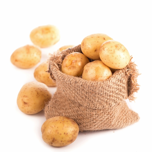 Raw potatoes in burlap bag isolated on white surface