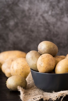 Raw potatoes in grey bowl
