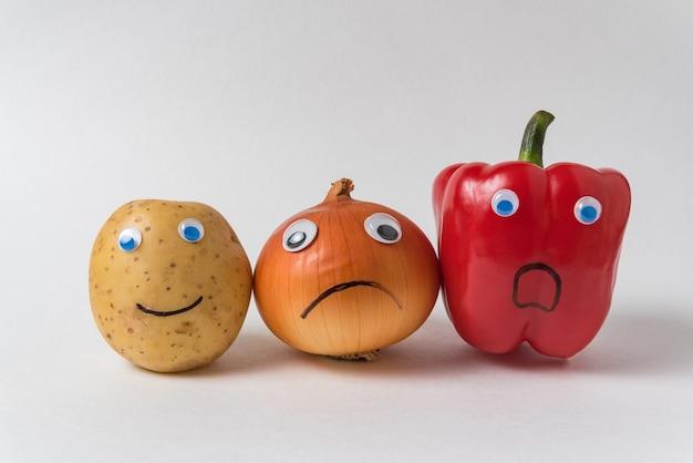 Сырой картофель, лук napiform и перец глазами googly на белом фоне. овощи с рожицами. концепция отличается от других.