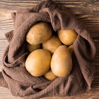 茶色の布に生のジャガイモ