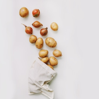 Raw potatoes and onion in eco-bag on white. organic healthy food background. flat lay, top view, copy space. grocery shopping food supermarket and zero waste concept.