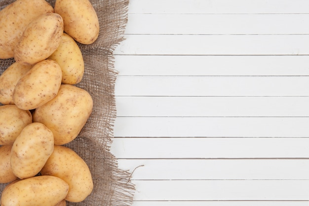 Raw potatoes with burlap on white