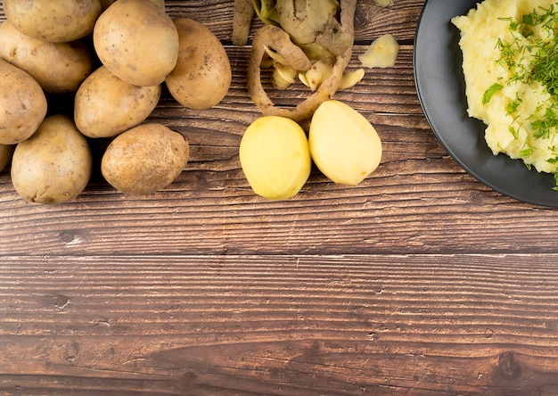 Raw potatoes on wooden background with copy space