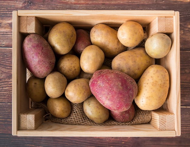 Raw potatoes in wooden box